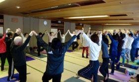 浜松トップ写真。全員で輪になって手を繋ぎ、両腕を天井に上げて片足立ちの木のポーズ。